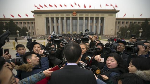 Eine Gruppe Journalisten belagert einen Politiker vor dem Parteikongress,