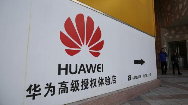 Leute stehen neben einem Logo von Huawei.