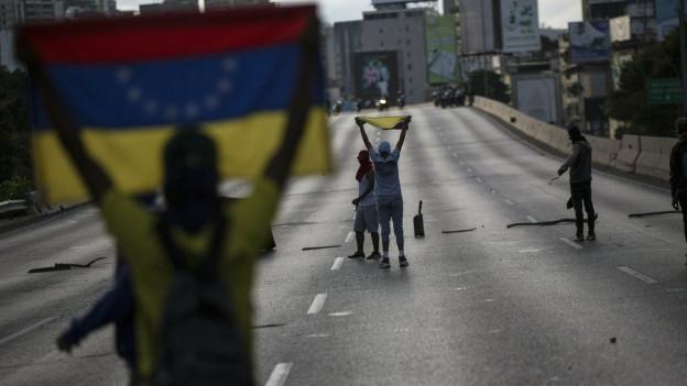 Zwei Personen mit venezolanischen Flaggen stehen auf einer fast leeren Strasse