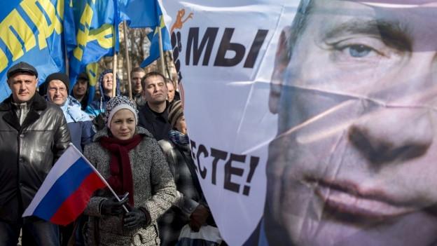 Menschenmenge auf der Krim mit einem Plakat, das den russischen Präsidenten Wladimir Putin zeigt.
