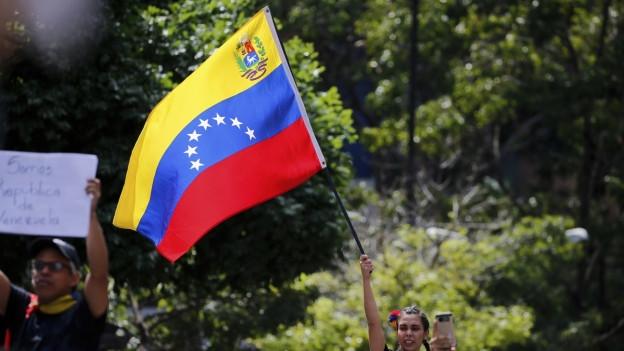 Eine Frau schwenkt eine venezolanische Flagge.