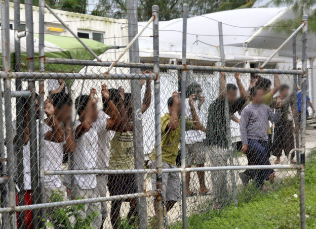 Auf dem Bild sind Flüchtlinge in den umstrittenen Lagern auf Manus und Dauru zu sehen die an einem Zaun stehen