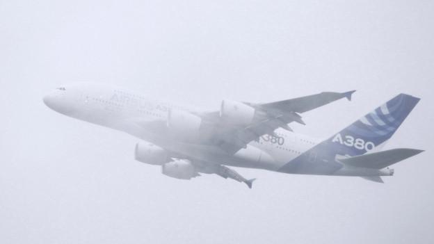 Ein A-380 fliegt durch Nebel.