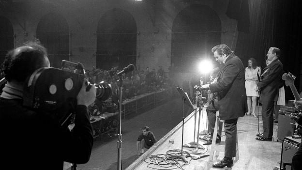 Johnny Cash, von der Seite gefilmt, steht im San Quentin-Gefängnis auf der Bühne.