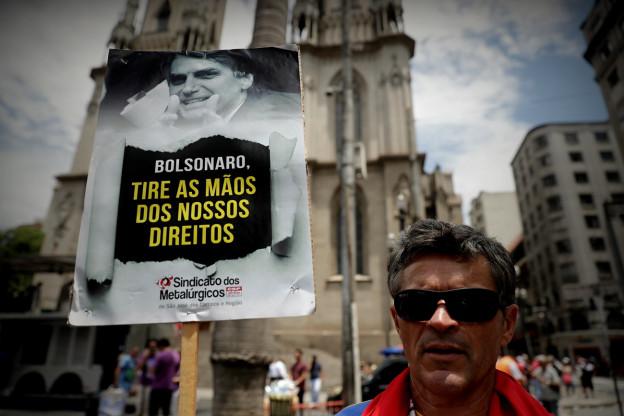 Ein Mann hält ein Protestplakat in die Höhe, auf der auch der brasilianische Präsident Jair Bolsonaro zu sehen ist.