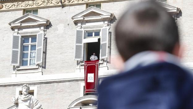 Kind hört dem Papst zu