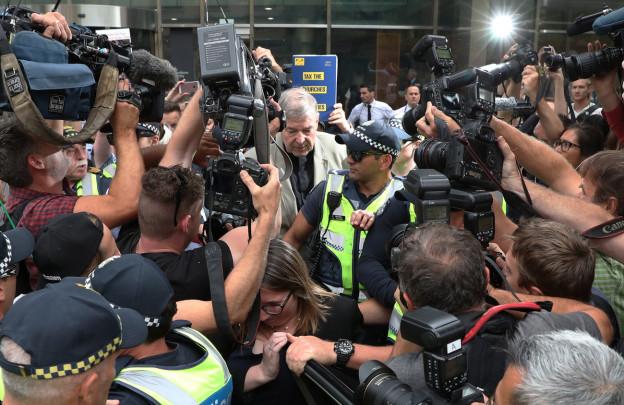 Ein älterer Mann wird von einem Polizisten geschützt während sich Fotografen und Kameraleute um ihn drängen.