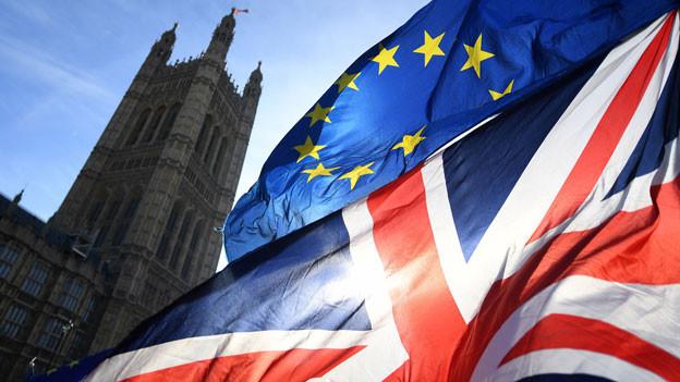 Fahnen der EU und Grossbritannien und im Hintergrund das Regierungsgebäude in London.