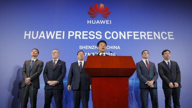 Das Bild zeigt einen Mann am Rednerpult und hinter ihm mehrere Männer an einer Pressekonferenz.
