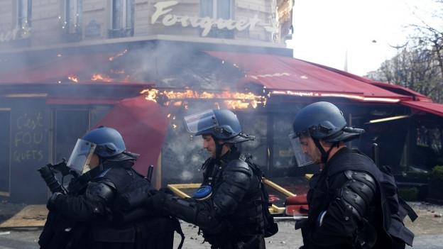 Polizisten stehen vor einem zerstörten Lokal in der Pariser Innenstadt (Proteste vom vergangenen Samstag 16.3.).