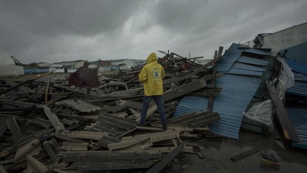 Das Bild zeigt zwei Personen, die über einen Haufen Trümmer steigen.