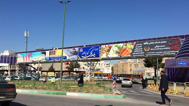 Strassenszene ausserhalb Teherans: Politische Botschaften neben Werbung für Teppiche und Cordon bleu vereint auf einer Plakatwand. Iran bleibt vielschichtig in seiner Krise.