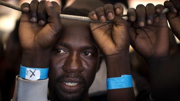 Flüchtlinge halten sich an einer Schnur fest