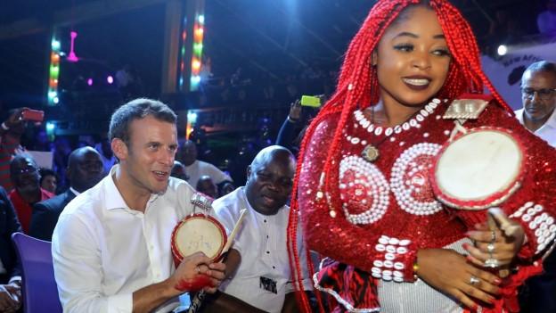 Der französische Präsident Macron mit afrikanischen Tänzern bei einem Staatsbesuch in Nigeria 2018.