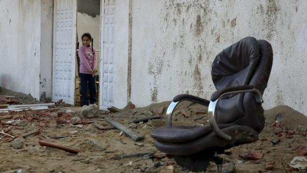 Ein Mädchen in einem zerstörten Haus.