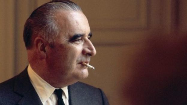 Georges Pompidou. Das Bild zeigt ihn im Profil mit einer Zigarette im Mund.