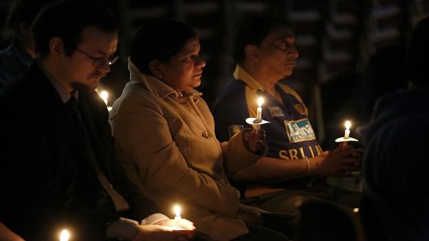 Menschen mit Kerzen in den Händen trauern.