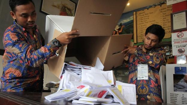 Zwei Wahlhelfer mit einer Box Wahlzetteln.