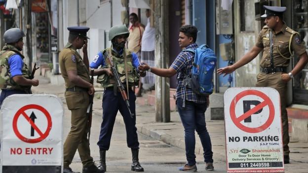 Das Bild zeigt bewaffnete Sicherheitskräfte, die in Sri Lanka Personenkontrollen durchführen.