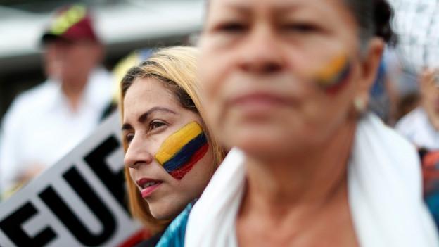 Zwei Frauen demonstrieren, beide haben die Flagge Venezuelas auf die Wange gemalt.