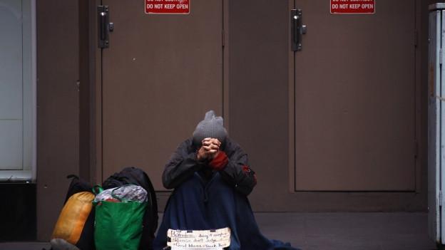 Ein obdachloser Mann bettelt auf einem Trottoir um Geld.