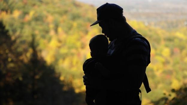 Ein Vater trägt sein Baby im Tragetuch.