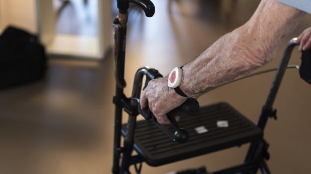 Ein älterer Mann an einem Rollator, der einen Nothandgelenksender trägt.