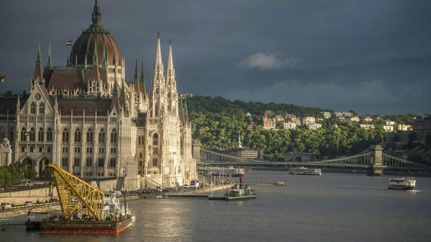 Ein Schiff mit Kran liegt vor dem Parlamentsgebäude, unweit der Unfallstelle in Budapest, Ungarn.