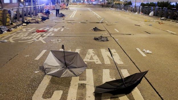 Kaputte Regenschirme liegen auf einer Hauptstrasse mitten in Hongkong.