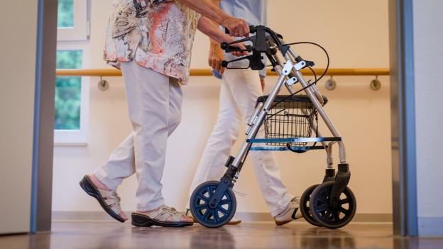 Eine alte Frau schiebt einen Rollator, eine Pflegefachkraft begleitet sie.