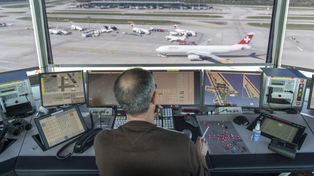 Ein Mitarbeiter von Skyguide kontrolliert die Monitore und hat Blick auf das Flugfeld, bei Skyguide im Tower des Flughafen Zürich Kloten.