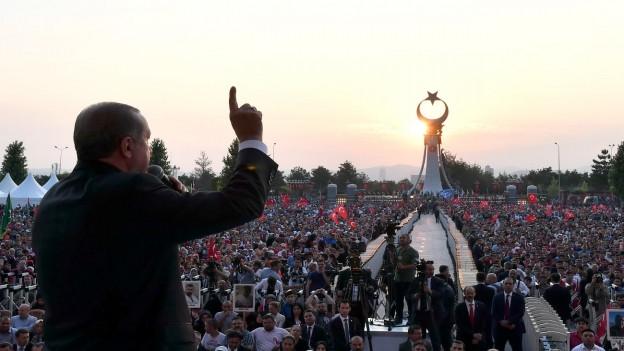 Menschenmenge mit Türkeifahnen jubeln Präsident Erdogan zu, der eine Rede hält zum Jahrestag nach dem Putschversuch.