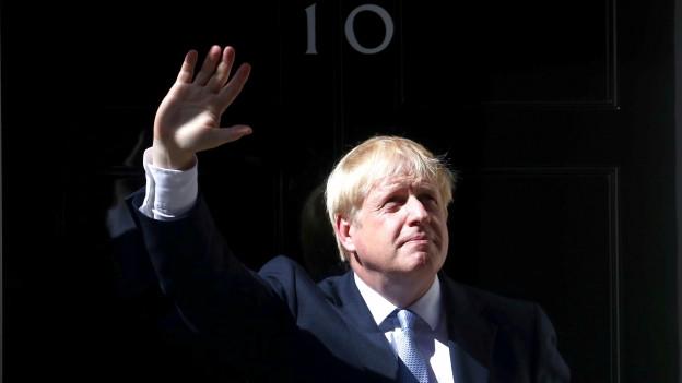 Boris Johnson steht vor der Türe zum Regierungssitz und winkt seinen Anhängern zu.