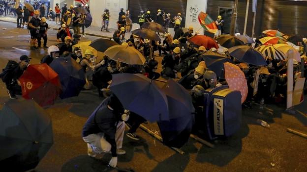 Das Bild zeigt Menschen, die gemeinsam am Boden kauern und Regenschirme hochhalten.
