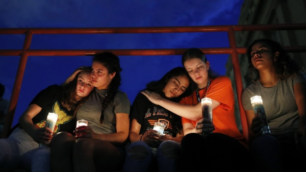 Das Bild zeigt Frauen, die Kerzen halten und sich umarmen.
