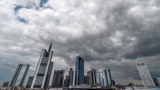 Dunkle Wolken über der Bankenskyline von Frankfurt am Main.