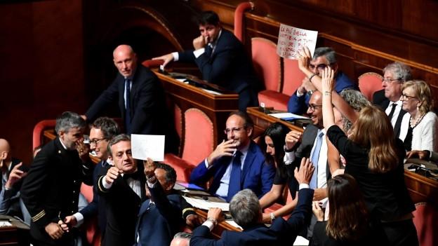 Im italienischen Senat zeigen Abgeordnete der demokratischen Partei auf Zetteln ihren Protest gegen Innenminister Salvini während der Debatte zur aktuellen Regierungskrise.