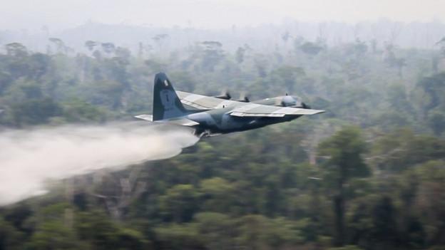 Auf dem Bild ist ein brasilianischer Militärjet zu sehen, der Wasser abwirft im Amazonasgebiet.