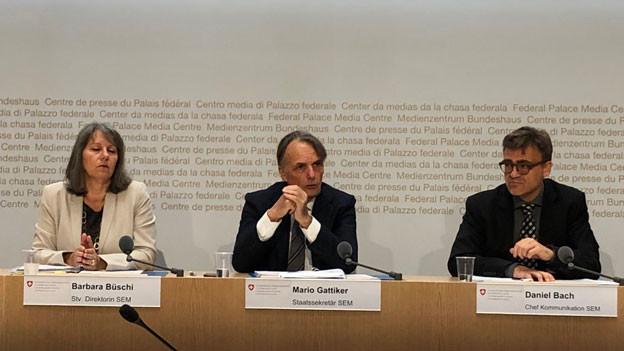 Mario Gattiker, Direktor des Staatssekretariats für Migration SEM (Mitte), Barbara Büschi, Stv. Direktorin (links) und Daniel Bach, Chef Kommunikation (rechts) an der Pressekonferenz in Bern.