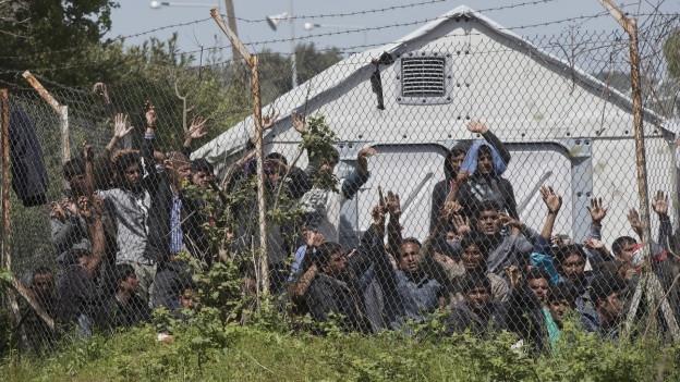 Das Bild zeigt Menschen hinter einem Stacheldrahtzaun im Flüchtlingslager Moria auf der griechischen Insel Lesbos.