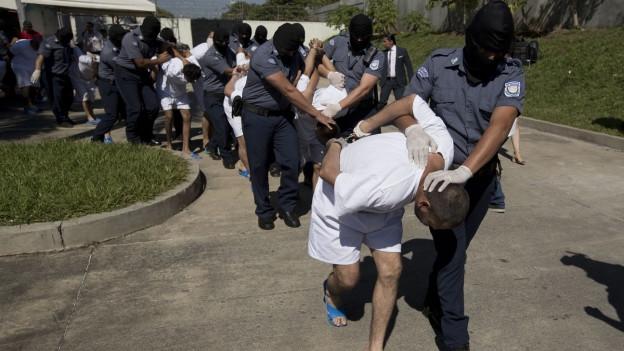 Mitglieder der Maras werden von Polizisten abgeführt