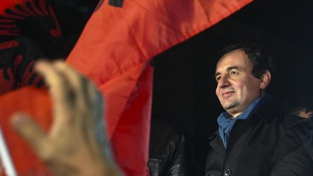 Zu sehen ist Albin Kurti, Gründer der kosovarischen Oppositionspartei Vetevendosje, umgeben von Fahnen.