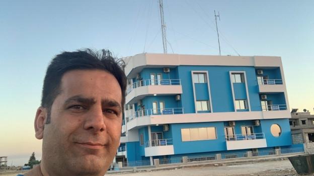 Auf dem Bild zu sehen ist der Direktor des nordsyrischen Radio ARTA FM, er macht ein Selfie vor einem blauen Gebäude mit Antennen auf dem Dach. Das ist das Gebäude, aus dem ARTA FM sendet.