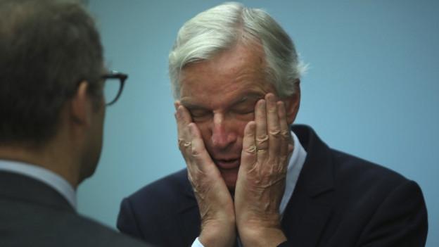 Ein Mann mit weissen Haaren streicht sich mit beiden Händen übers Gesicht, die Augen sind geschlossen.