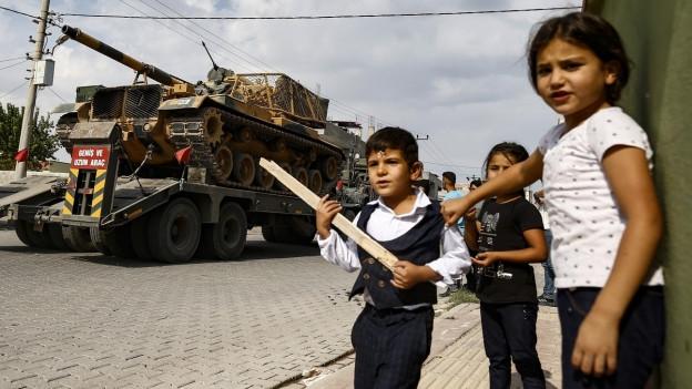 Kinder stehen am Strassenrand, auf der Strasse steht ein Lastwagen, beladen mit einem Kampfpanzer.