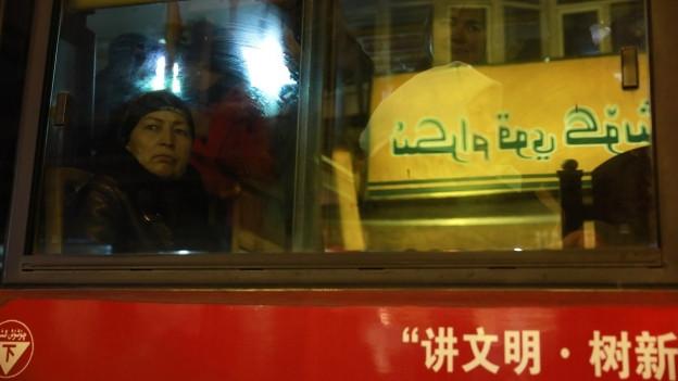 Uiguren blicken aus einem chinesischen Bus.