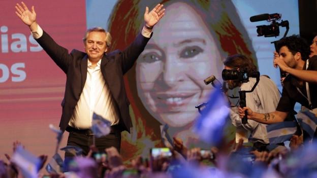 Der peronistische Präsidentschaftskandidat Alberto Fernández winkt seinen Anhängern vor einem großen Bild seiner Kollegin, der ehemaligen Präsidentin Cristina Kirchner, zu.