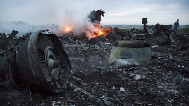 Flugzeug-Wrackteile liegen am Boden und brennen zum Teil.