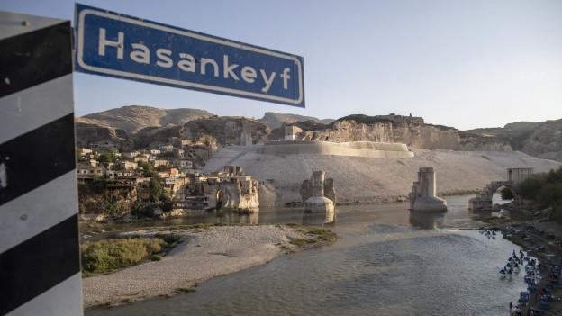 Stadtansicht mit Ortsschild und Sicht auf gebaute Staumauern am Tigris.