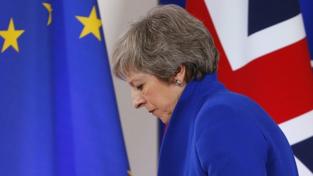 Theresa May vor EU-Flagge und Union Jack.